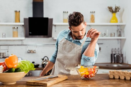 handsome young man in apron adding salt to vegetable salad while cooking in kitchen