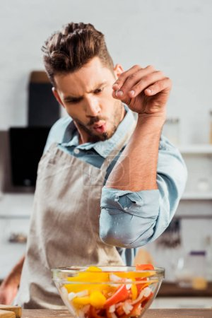 Photo for Handsome young man in apron adding salt to vegetable salad - Royalty Free Image