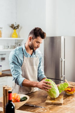 Photo for Young man in apron holding napa cabbage and cooking in kitchen - Royalty Free Image