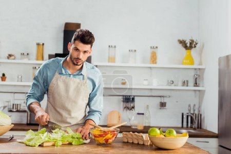 Photo for Handsome young man in apron chopping vegetables and looking at camera in kitchen - Royalty Free Image