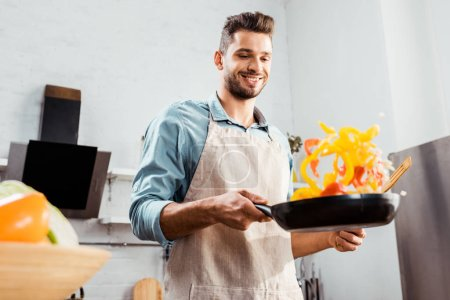Photo for Low angle view of smiling young man in apron holding frying pan with vegetables - Royalty Free Image