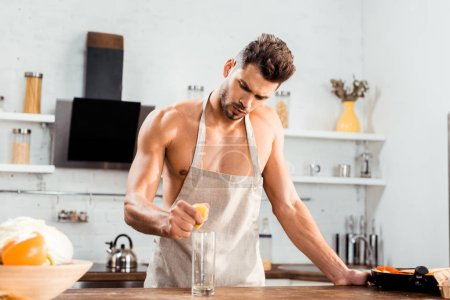 Photo for Sexy young man in apron squeezing lemon in glass - Royalty Free Image
