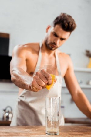 Photo for Close-up view of bare-chested young man in apron squeezing lemon in glass - Royalty Free Image