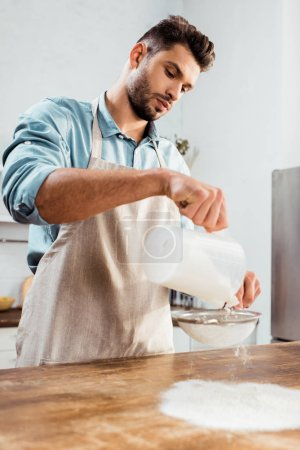 Photo for Low angle view of handsome young man in apron sifting flour on kitchen table - Royalty Free Image