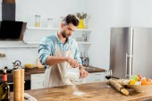 handsome young man in apron sifting flour on kitchen table