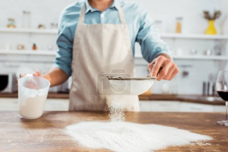 Photo for Partial view of young man in apron sifting flour on kitchen table - Royalty Free Image