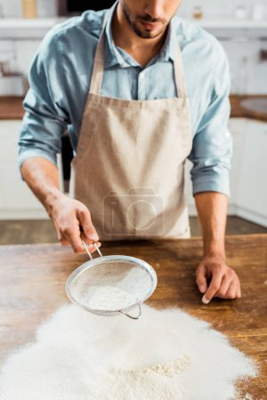 Photo for Cropped shot of young man in apron sifting flour on kitchen table - Royalty Free Image
