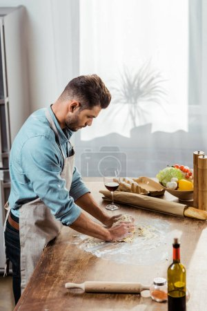 Photo for High angle view of young man in apron preparing dough in kitchen - Royalty Free Image