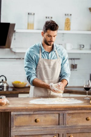 Photo for Focused young man in apron preparing dough in kitchen - Royalty Free Image