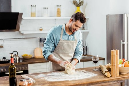 Photo for Smiling young man in apron preparing dough in kitchen - Royalty Free Image
