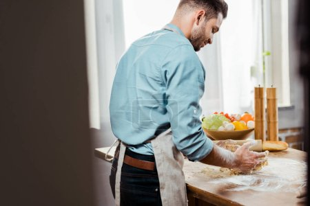 back view of young man in apron preparing dough in kitchen