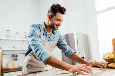 Photo for Smiling young man in apron with rolling pin preparing dough in kitchen - Royalty Free Image