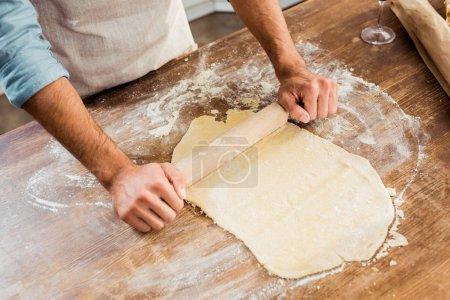 Schuss auf jungen Mann in Schürze mit Nudelholz und Teigzubereitung in Küche
