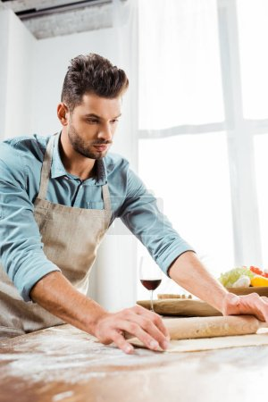 Photo for Handsome young man in apron holding rolling pin and preparing dough in kitchen - Royalty Free Image