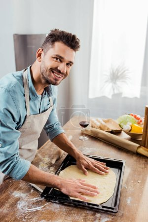 Photo for Smiling young man in apron preparing pizza dough on baking tray - Royalty Free Image