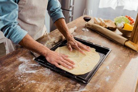 cropped shot of man preparing pizza dough on baking tray