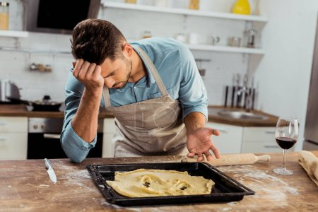 Photo for Upset young man in apron leaning at table with spoiled dough on baking tray - Royalty Free Image
