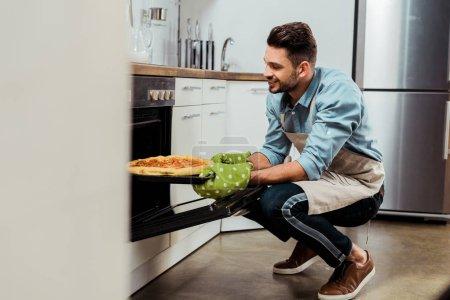 joven sonriente en delantal sacando bandeja para hornear con pizza del horno