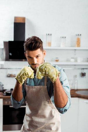 Photo pour Beau jeune homme en tablier et maniques boxe et regardant la caméra pendant la cuisson dans la cuisine - image libre de droit