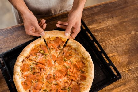 cropped shot of man holding pizza slice on baking tray