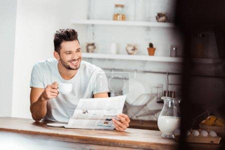 enfoque selectivo de la sonriente joven sosteniendo la taza de café y leyendo el periódico en la cocina por la mañana