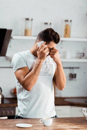 Photo pour Pont de nez de frottement jeune frustré et parler de smartphone au matin dans la cuisine - image libre de droit