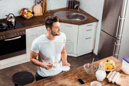 Photo pour Vue grand angle du jeune homme souriant tenant une tasse de café et regardant loin dans la cuisine - image libre de droit