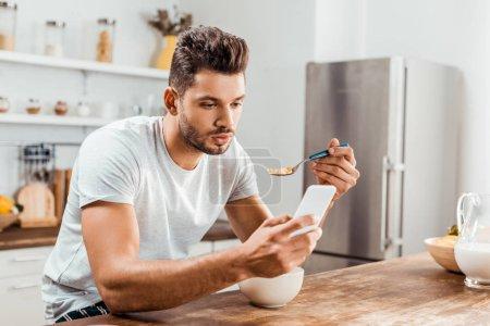 Photo pour Beau jeune homme utilisant un smartphone et prenant le petit déjeuner à la maison - image libre de droit