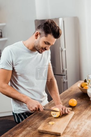 Photo for Smiling young man in pajamas cutting lemon on chopping board in kitchen - Royalty Free Image
