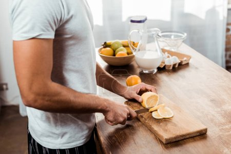 Photo for Mid section of young man cutting lemon on chopping board - Royalty Free Image