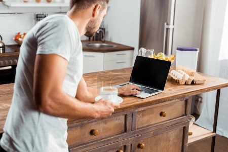 Photo for Cropped shot of young man holding cup of coffee and using laptop with blank screen in kitchen - Royalty Free Image