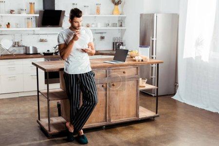 Photo pour Beau jeune homme en pyjama boire du café dans la cuisine - image libre de droit