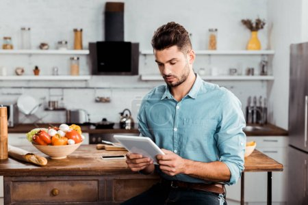 Photo pour Beau jeune homme à l'aide de tablette numérique pendant la cuisson dans la cuisine - image libre de droit