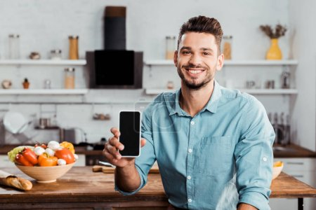 handsome young man holding smartphone with blank screen and smiling at camera in kitchen