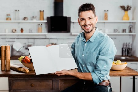 Photo for Handsome young man holding blank cookbook and smiling at camera in kitchen - Royalty Free Image