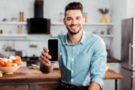 Photo pour Beau jeune homme tenant smartphone avec écran blanc et souriant à la caméra dans la cuisine - image libre de droit