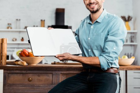 Photo for Cropped shot of smiling young man holding blank cookbook in kitchen - Royalty Free Image