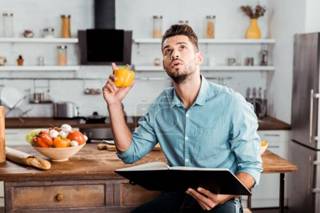 Photo for Young man holding fresh pepper and cookbook while sitting in kitchen and looking up - Royalty Free Image