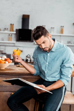 Photo for Focused young man holding fresh pepper and reading cookbook in kitchen - Royalty Free Image