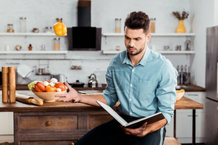 handsome young man throwing fresh pepper and reading cookbook in kitchen