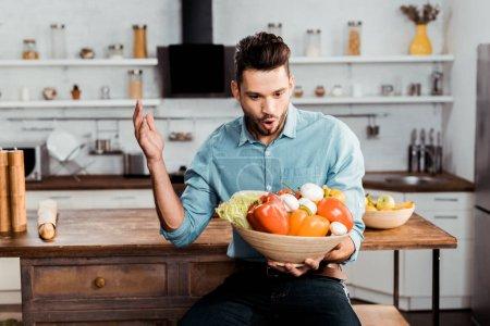 Photo pour Excité jeune homme tenant bol avec des légumes frais dans la cuisine - image libre de droit
