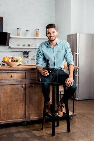 Photo for Handsome young man holding bottle of beer and smiling at camera in kitchen - Royalty Free Image