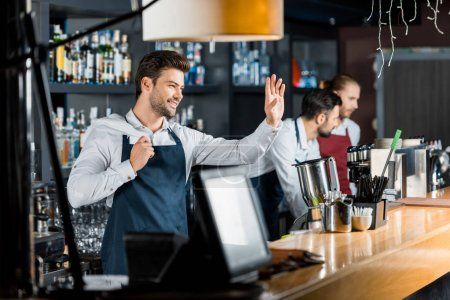 smiling handsome barman with cloth greeting at workplace