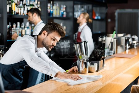 adult handsome barman cleaning wooden counter with cloth