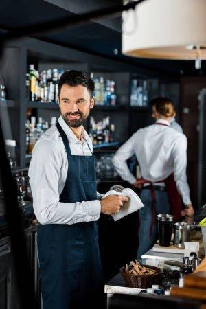 smiling handsome bartender polishing glass near counter