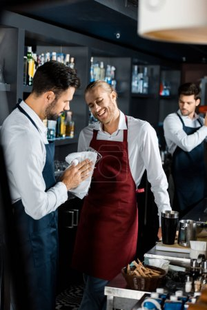 cheerful smiling barmen standing at workplace while coworker polishing glass