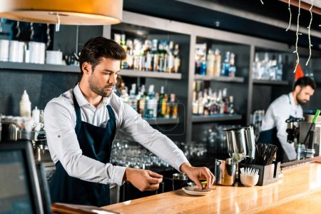 handsome barista putting sugar sticks and spoon on saucer at counter