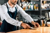 close up of barman putting sugar sticks and spoon on saucer at counter