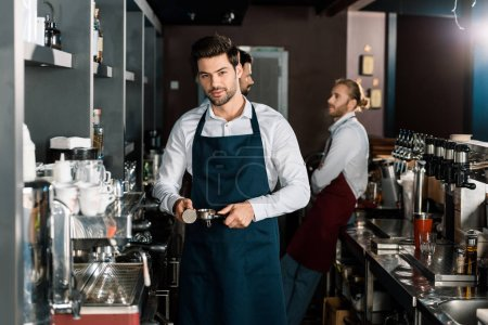 handsome barista in apron making coffee at workplace