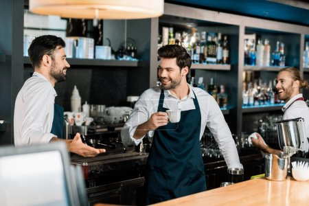 handsome cheerful barman drinking coffee and speaking with colleagues at workplace